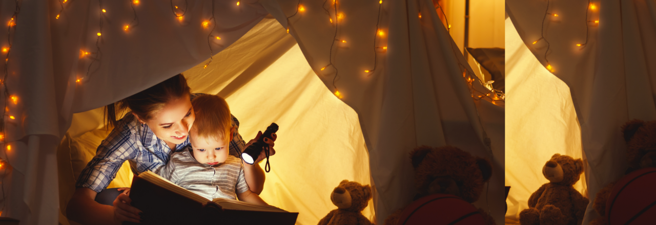 Mother and Daughter Reading Under A Blanket Fort in Bedroom